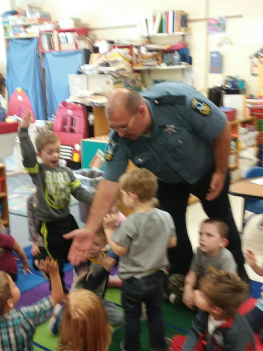 Officer Joe gives high fives to the Pre-K students.