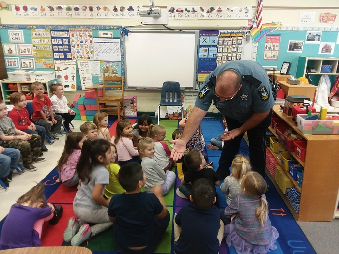 The morning pre-k class gives high fives to Officer Joe.