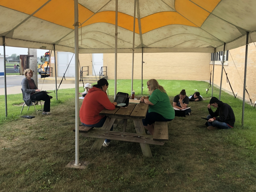 Mrs. Brazel's class outside reading under the tent.